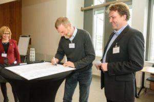 Hugo Kirchhelle unterzeichnet unter den Augen von Dr. Elisabeth Schwenzow, Geschäftsführerin der Euregio, und Mirko Wohlrabe den Pakt.